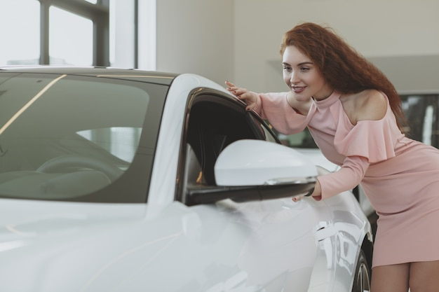 Junges geschäftsfraueinkaufen für neuwagen am verkaufsstellenausstellungsraum