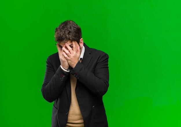 Junges geschäftsmannbedeckungsgesicht mit den händen, spähend zwischen finger mit überraschtem ausdruck und schauen zur seite gegen grünen hintergrund