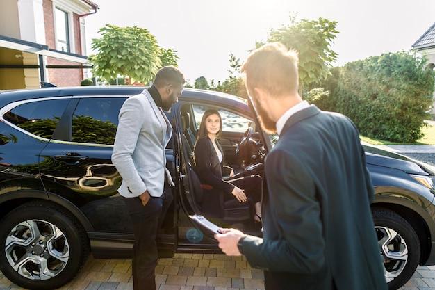 Junges geschäftspaar, afrikanischer mann und kaukasische frau, auf der suche nach auto zu kaufen, frau sitzt im auto, mann steht und lächelt. rückansicht des händlers, der den vertrag hält