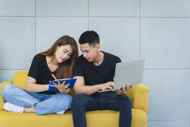 Junges glückliches asiatisches geschäft sme onwer paar in der freizeitkleidung mit smileygesicht benutzt laptop und überprüft produkt auf lager und schreibt in das klemmbrett an ihrem starthauptbüro, lieferer