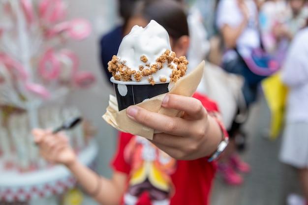 Junges glückliches asiatisches mädchen, das ihre weiche sahne, japanische eiscreme, mit granolabelag genießt