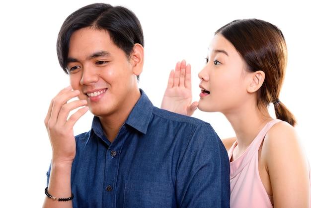 Junges glückliches asiatisches paar, das mit frau lächelt, die zum mann flüstert