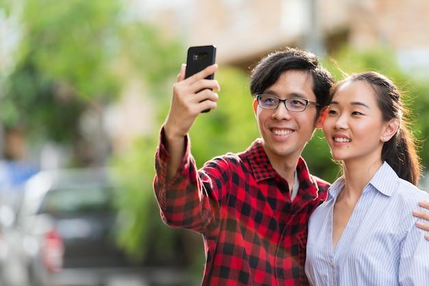 Junges glückliches asiatisches paar, das selfie zusammen im freien nimmt
