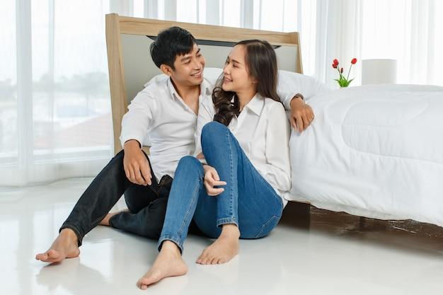 Junges glückliches attraktives asiatisches paar, das sauberes weißes hemd trägt, das zusammen auf dem bodenschlafzimmer sitzt