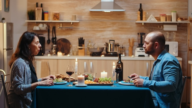 Junges glückliches ehepaar, das während des romantischen abendessens videoanruf in der küche hat und festliches essen isst. pov online-internet-moderne konferenz, chatten, kommunikation, chat-gesprächsanruf über webcam