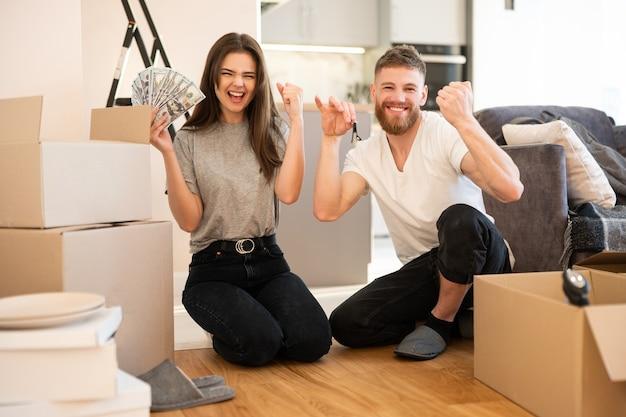 Junges glückliches europäisches paar, das im neuen zuhause feiert. mädchen, das dollarbanknoten hält. kerl, der schlüssel hält. kartons mit sachen. konzept des einzugs in eine neue wohnung. junge familie. studio-wohnung interieur