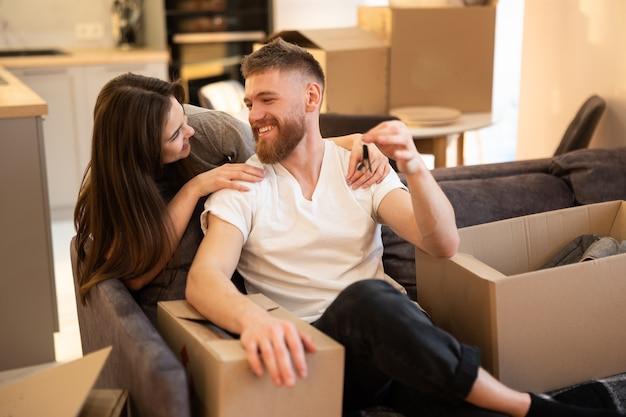 Junges glückliches europäisches paar, das im neuen zuhause feiert. mann, der auf sofa sitzt und schlüssel hält. kartons mit sachen. konzept des einzugs in eine neue wohnung. idee einer jungen familie. interieur des studio-apartments