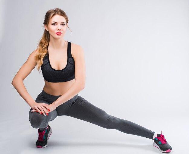 Junges glückliches fitnessmädchen mit sportlichem körper