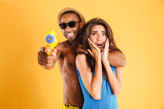 Junges glückliches gemischtrassiges paar, das spaß hat, mit wasserpistolen zu spielen, die auf der orange wand lokalisiert werden