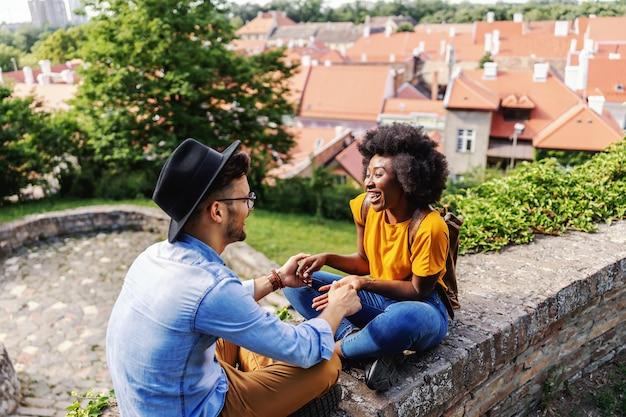 Junges glückliches hipster-paar, das draußen in einem alten teil der stadt sitzt, hände hält und flirtet