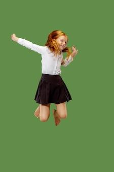 Junges glückliches kaukasisches jugendlich mädchen, das in die luft springt, lokalisiert auf grünem studiohintergrund. schönes weibliches halblanges porträt.