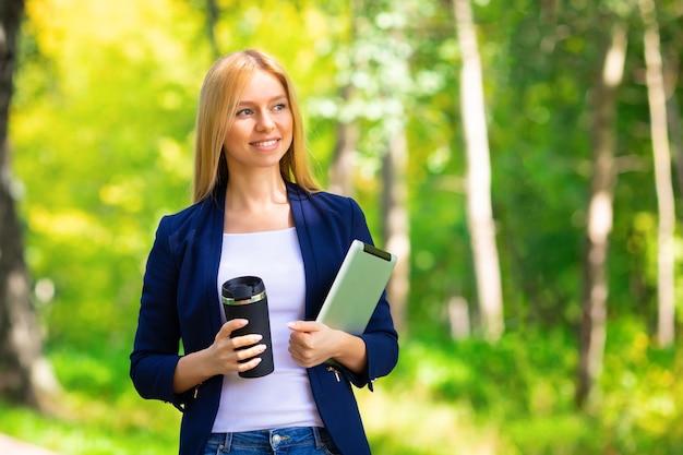 Junges glückliches lächelndes erwachsenes mädchen des kaukasischen erfolgs, das im park mit tablette und telefon geht