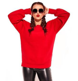 Junges glückliches lächelndes frauenmodell mit hellem make-up und den bunten lippen mit zwei zöpfen und sonnenbrille in der roten kleidung des sommers lokalisiert. luft küssen