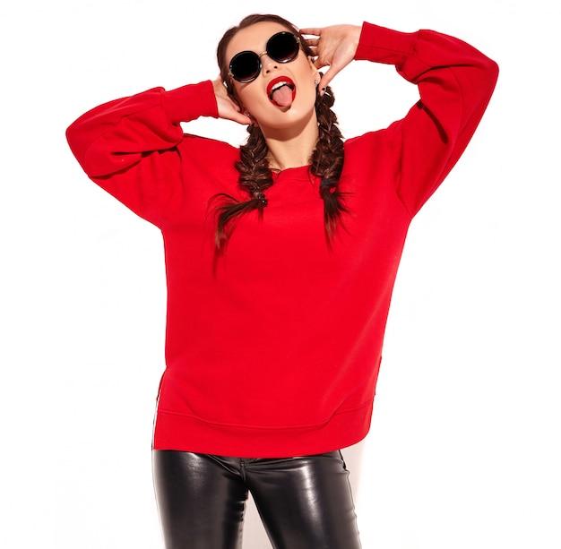 Junges glückliches lächelndes frauenmodell mit hellem make-up und den bunten lippen mit zwei zöpfen und sonnenbrille in der roten kleidung des sommers lokalisiert. zeigt ihre zunge