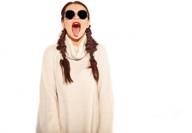 Junges glückliches lächelndes frauenmodell mit hellem make-up und den roten lippen mit zwei zöpfen in der warmen strickjackenkleidung des sommers lokalisiert. zeigt ihre zunge