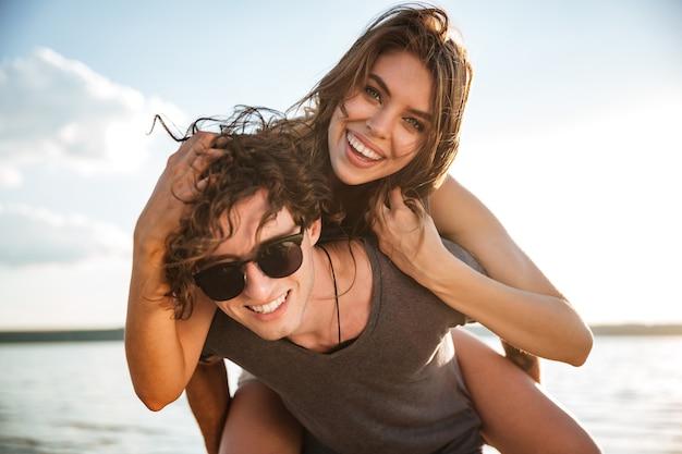 Junges glückliches lächelndes paar verliebt huckepack am strand