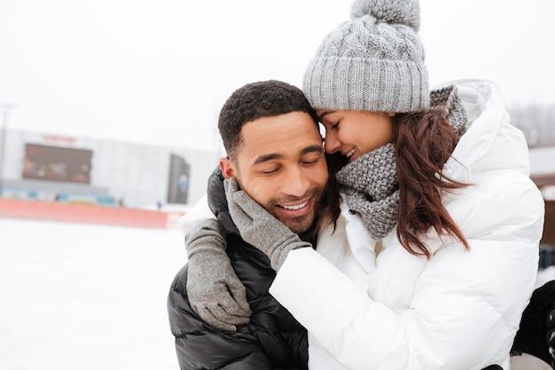 Junges glückliches liebendes paar, das an der eisbahn umarmt und skatet