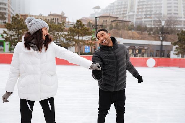 Junges glückliches liebendes paar, das an eisbahn im freien skatet