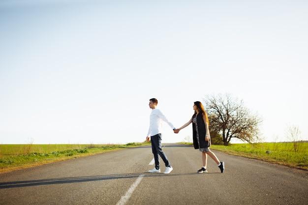 Junges, glückliches, liebevolles paar, das auf der straße händchen haltend steht und sich ansieht