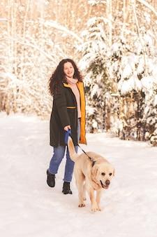 Junges glückliches mädchen geht mit hund labrodor im winterpark
