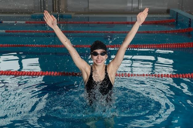 Junges glückliches mädchen mit brille und mütze, das im schwimmbad springt Premium Fotos