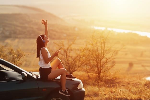 Junges glückliches mädchen mit kopfhörern hören musik, halten telefon in der hand. sie sitzt draußen auf der motorhaube eines autos.