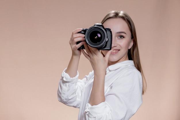 Junges glückliches mädchen nimmt bilder mit digitalkamera auf. arbeit, menschen, hobby, lifestyle, technologie, studienkonzept