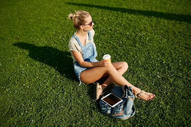 Junges glückliches mädchen trinkt kaffee draußen sitzend auf gras