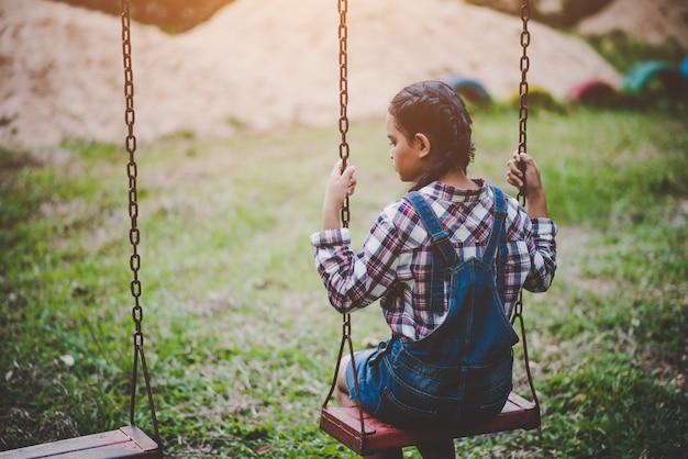 Junges glückliches mädchenreiten auf einem schwingen im park