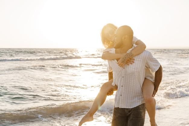 Junges glückliches paar an der küste, das das meer genießt
