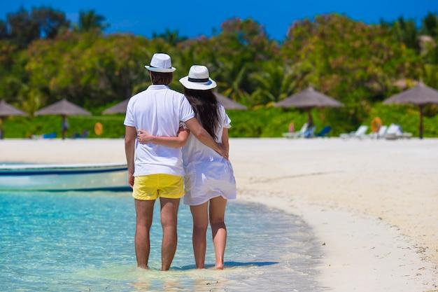 Junges glückliches paar auf weißem strand an den sommerferien