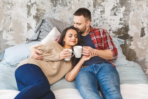 Junges glückliches paar, das am morgen kaffee oder tee im bett trinkt.