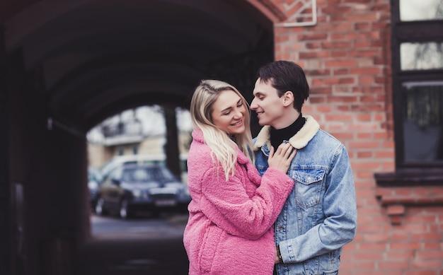 Junges glückliches paar, das am valentinstag lächelt und durch die stadt geht