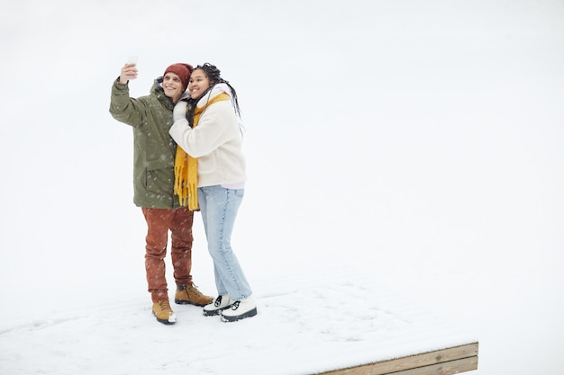 Junges glückliches paar, das an der kamera lächelt, während selfie-porträt auf handy während ihres spaziergangs im winter macht