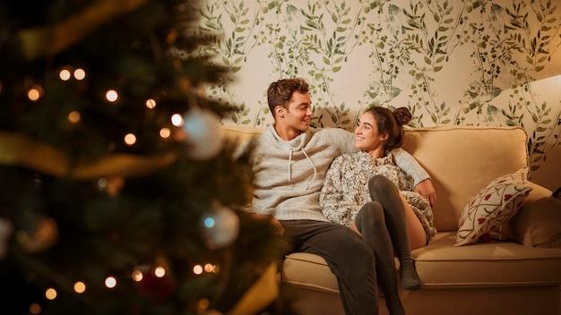 Junges glückliches paar, das auf couch sitzt