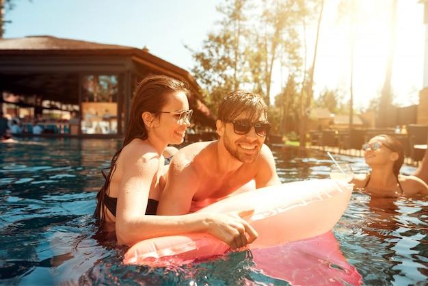Junges glückliches paar, das auf luftmatratze im pool stillsteht