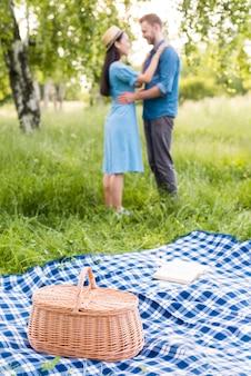 Junges glückliches paar, das auf picknick in der natur tanzt