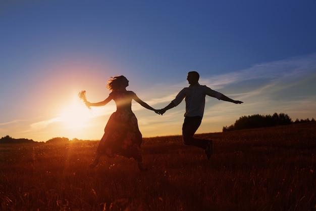 Junges glückliches paar, das auf sonnenuntergang springt
