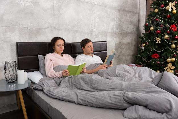 Junges glückliches paar, das bücher liest, während es im bett liegt und pyjamas im schlafzimmer mit weihnachtsbaum trägt