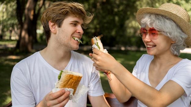 Junges glückliches paar, das burger im park isst
