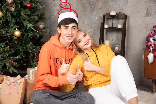 Junges glückliches paar, das daumen nahe dem weihnachtsbaum umarmt und aufgibt.