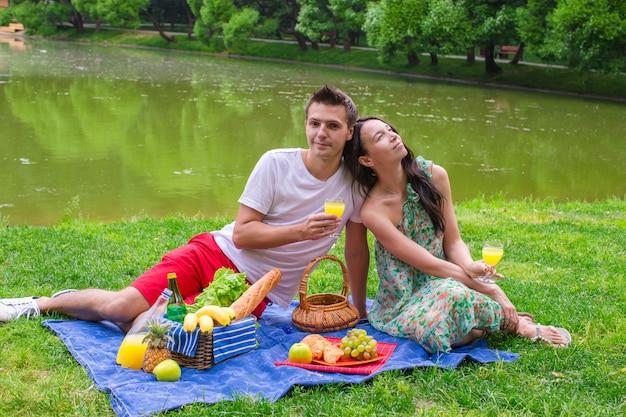 Junges glückliches paar, das draußen picknickt und sich entspannt
