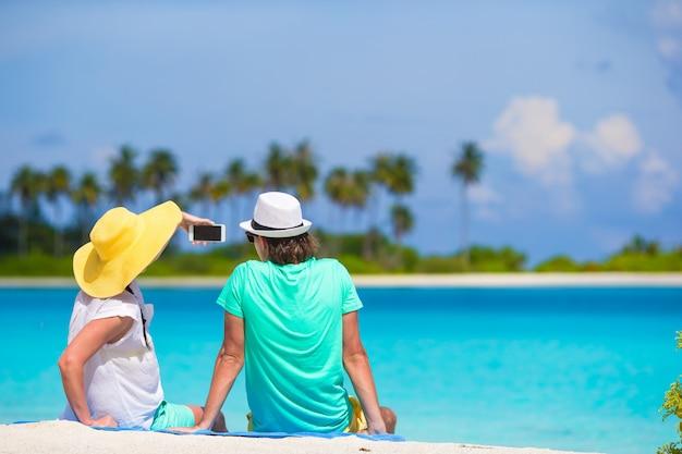 Junges glückliches paar, das ein selfie mit handy auf strand macht