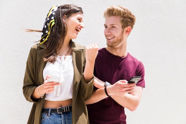 Junges glückliches paar, das einander hält mobiltelefon gegen den weißen hintergrund betrachtet