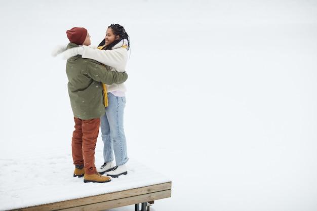 Junges glückliches paar, das einander umarmt, das auf der holzbrücke während ihres spaziergangs im winter steht