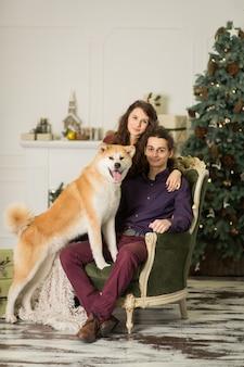 Junges glückliches paar, das entzückenden hund akitas inu streichelt, während sie auf stilvollem retro- lehnsessel für weihnachtsfeiertage zu hause sitzen.