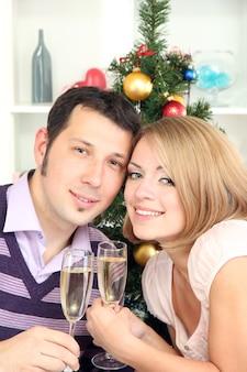 Junges glückliches paar, das gläser mit champagner am tisch nahe weihnachtsbaum hält