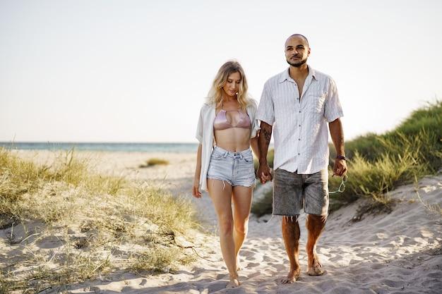 Junges glückliches paar, das händchen hält und am sommertag zusammen zum strand geht?
