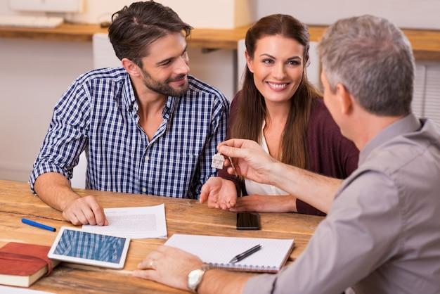 Junges glückliches paar, das hausschlüssel vom immobilienmakler erhält. dem jungen paar die schlüssel für ein neues haus geben. lächelndes paar, das finanzvertrag für hypothek unterzeichnet.