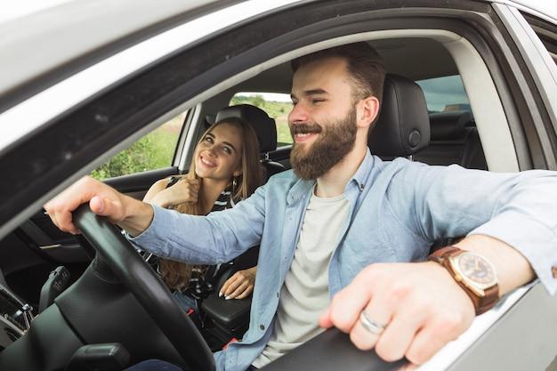Junges glückliches paar, das im auto sitzt
